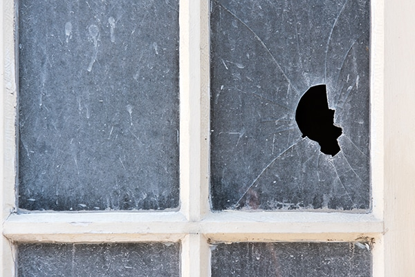 Broken shattered pane of glass with a gaping hole through it in an old opaque window with wooden frame