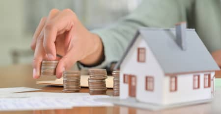 person stacking coins next to a small house