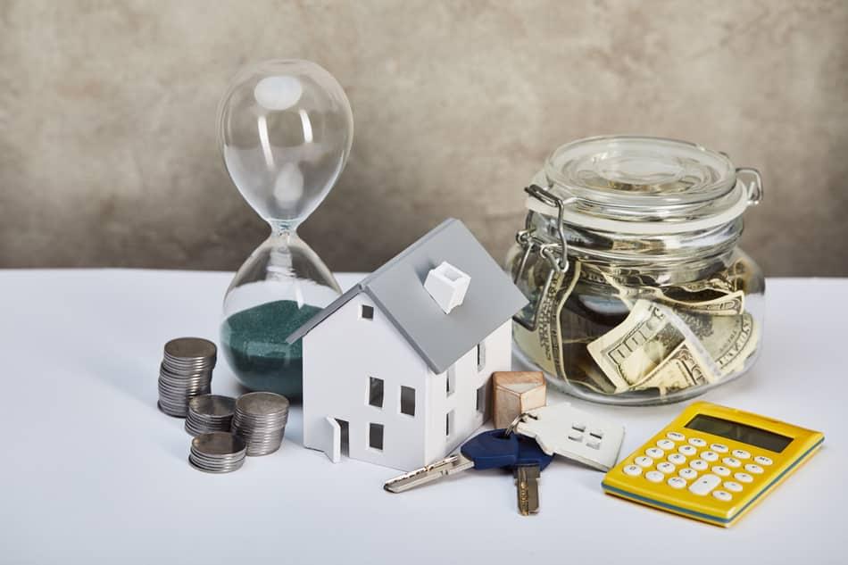 small house, keys, calculator, and money