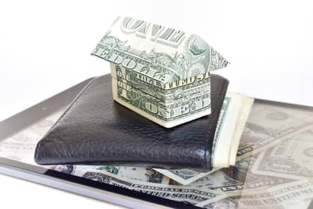 small house made of paper bill on top of wallet